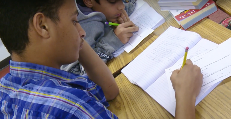 Two students writing in notebooks