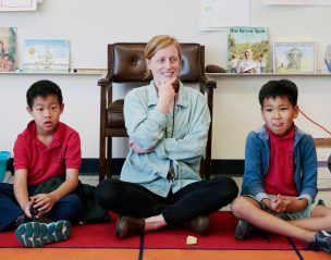 A teacher scholar sits with her students on the rug