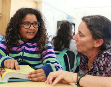 Student and teacher talking about reading